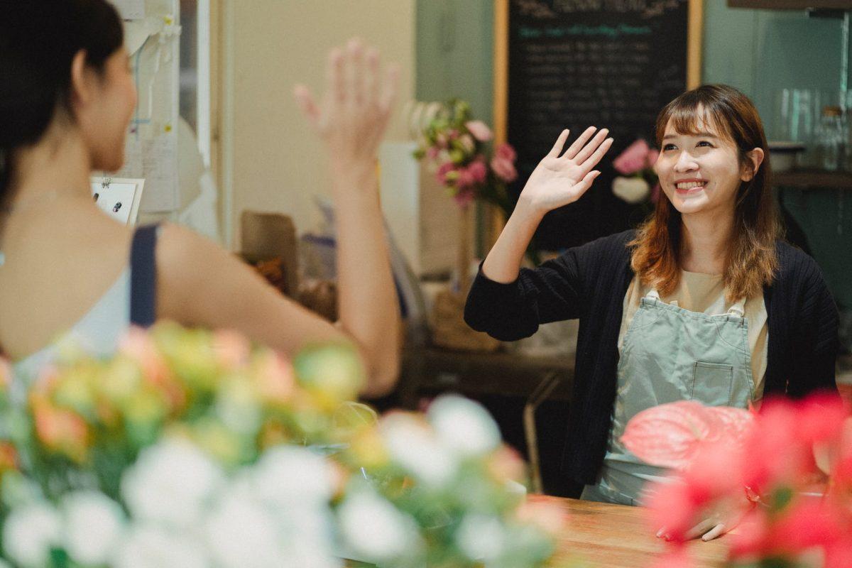 happy female florist waving hand in shop